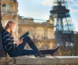 Beautiful young woman in Paris, reading a book